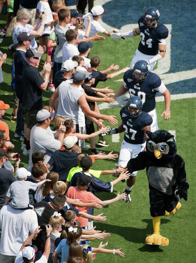 Rice players follow their mascot as they high five fans while taking the field to face Marshall in a college football game at Rice Stadium, Saturday, Sept. 22, 2012, in Houston. Photo: Smiley N. Pool, Houston Chronicle / © 2012  Houston Chronicle