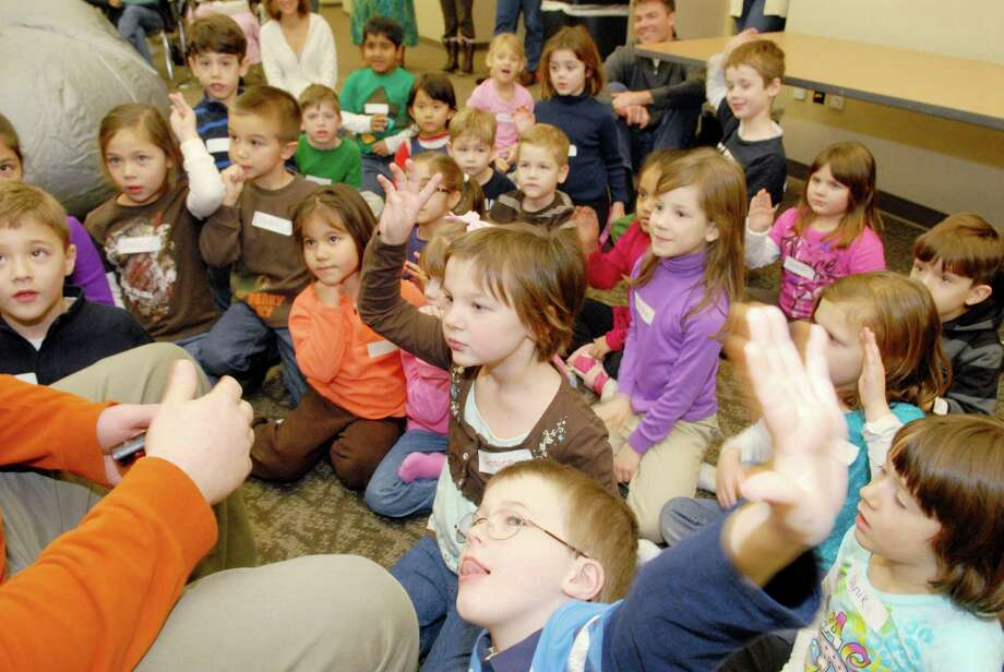"""In the center surrounded by others in the group, with her hand up, Jessica Shook, age 5, of Clifton Park, has a question for Chris Grubb of Planetarium Adventures as he conducts his program encouraging children to """"reach for the stars"""" at the """"Starlab Learning Dome"""" at the Clifton Park-Halfmoon Public Library in Clifton Park, NY, on Thursday, Dec. 30, 2010.  Grubb, of Planetarium Adventures of Balston Spa, brings the inflatable dome with a planetarium devise, around and presents the education programs in various venues.     (Luanne M. Ferris / Times Union) Photo: Luanne M. Ferris / 00011449A"""