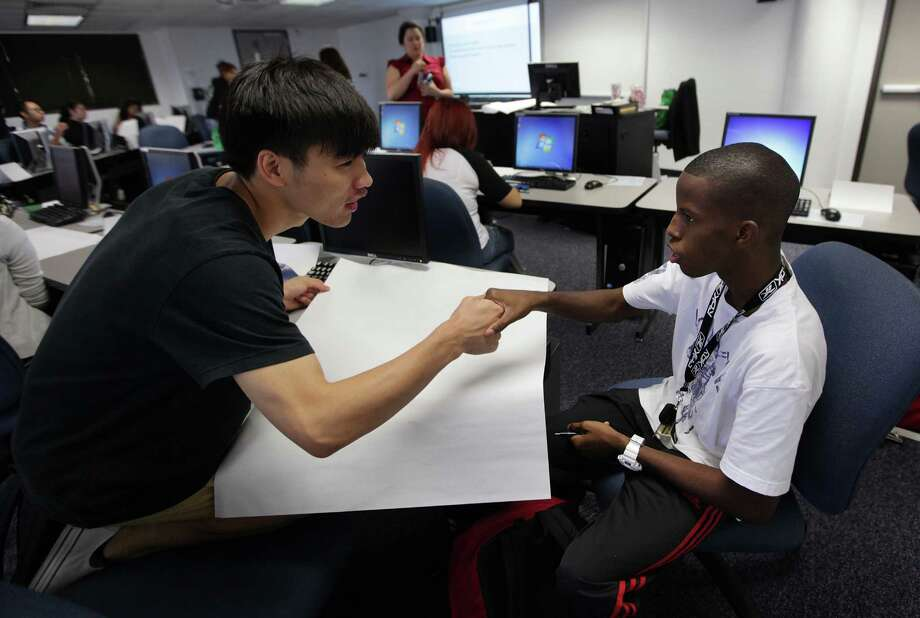 Jiawer Guan, left, and Michael Hopkins get acquainted Thursday before their freshman seminar course at the University of Houston- Downtown. Photo: Mayra Beltran / © 2012 Houston Chronicle