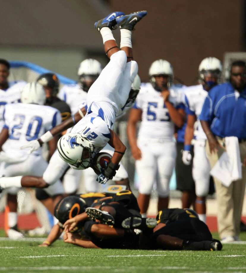 Dekaney's Travarius Brown (21) goes head over heels as he is upended by the Klein Oak defense on the opening kickoff of Saturday's District 13-5A game at Klein Memorial Stadium. Brown also rushed for 50 yards on six carries. Photo: Eric Christian Smith