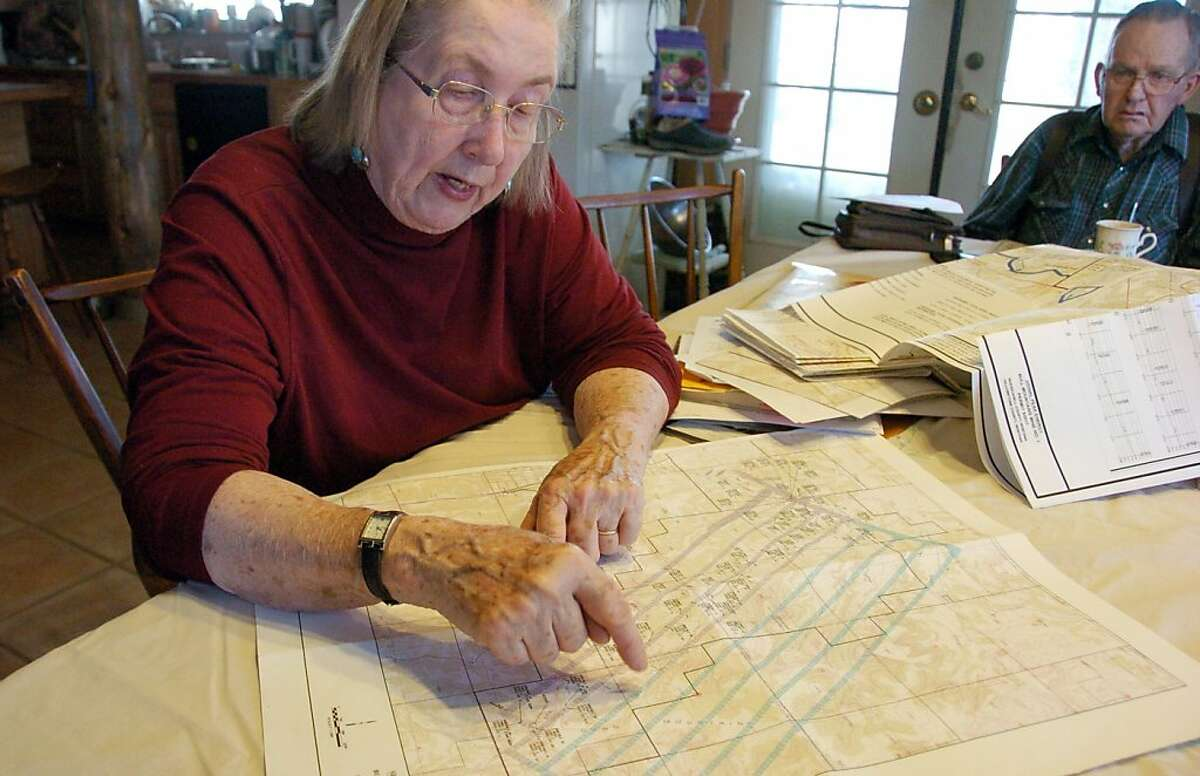 This April 23, 2012 photo shows Ellen Pfister looking over a map depicting the Bull Mountain Mine that reaches beneath her ranch as husband Don Golder looks on from their house south of Roundup, Mont. Rising U.S. coal exports that the industry hopes can offset flagging domestic demand are reviving worries among some Montana ranchers that their way of life could be sacrificed to feed Asian energy demands. Near the town of Roundup, the once-shuttered Bull Mountain mine could produce more than 9 million tons of coal this year, more than half headed overseas. (AP Photo/ReporterMatt Brown)