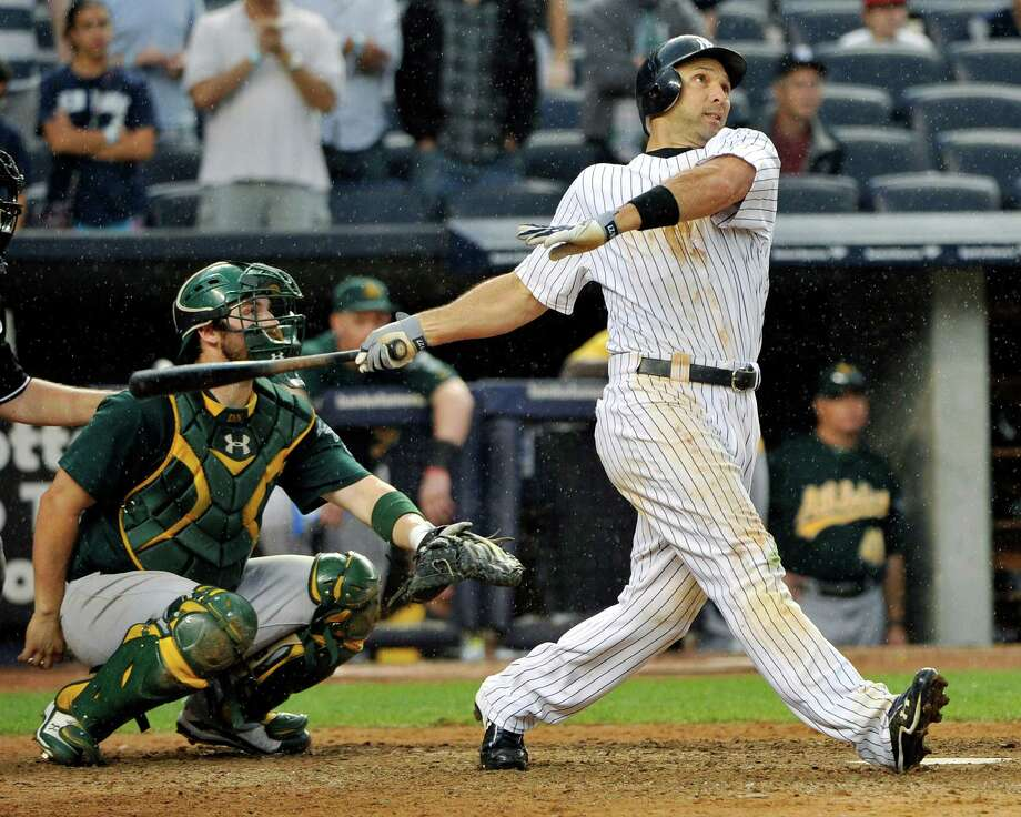 New York Yankees' Raul Ibanez hits a home run as Oakland Athletics catcher George Kottaras, left, looks on during the 13th inning of a baseball game Saturday, Sept. 22, 2012, at Yankee Stadium in New York. The Yankees defeated the Athletics 10-9 in 14 innings. (AP Photo/Bill Kostroun) Photo: Bill Kostroun