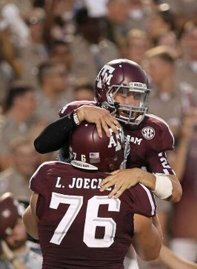 Texas A&M University quarterback Johnny Manziel (2) jumps into  offensive linesman Luke Joeckel's (7
