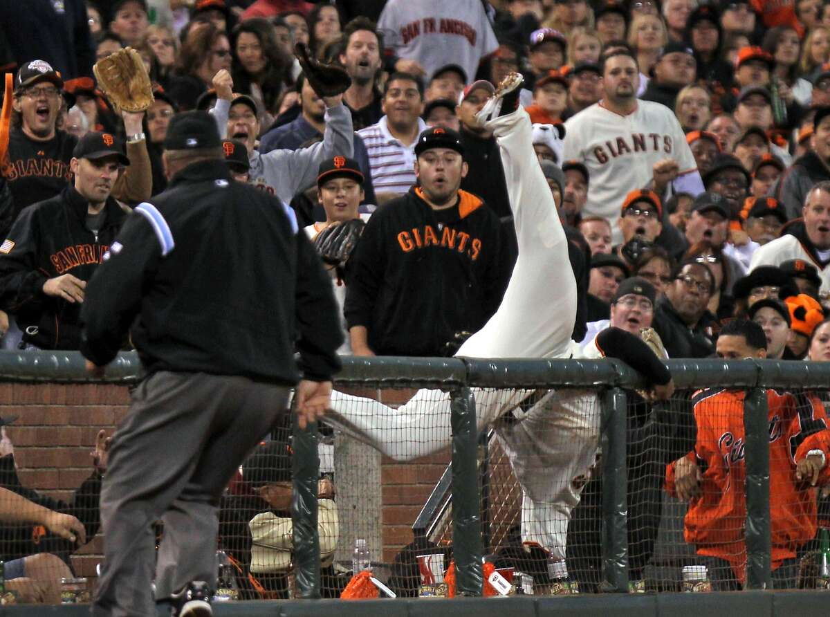 San Francisco Giants Pablo Sandoval falls over the third base fence after catching San Diego Padres Yonder Alonso foul ball in the fourth inning of their MLB baseball game Saturday September 22, 2012. In San Francisco California.