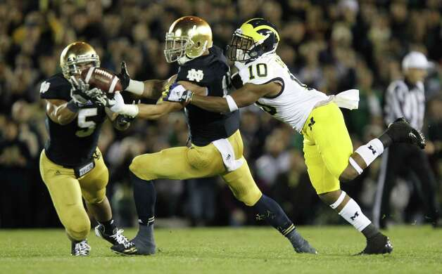 Notre Dame Notre Dame linebacker Manti Te'o, left. intercepts a pass intended for Michigan's Jeremy Gallon, right, in the second quarter at Notre Dame Stadium in South Bend, Indiana, Saturday, September 22, 2012. (Julian H. Gonzalez/Detroit Free Press/MCT) Photo: Julian H. Gonzalez, McClatchy-Tribune News Service / Detroit Free Press