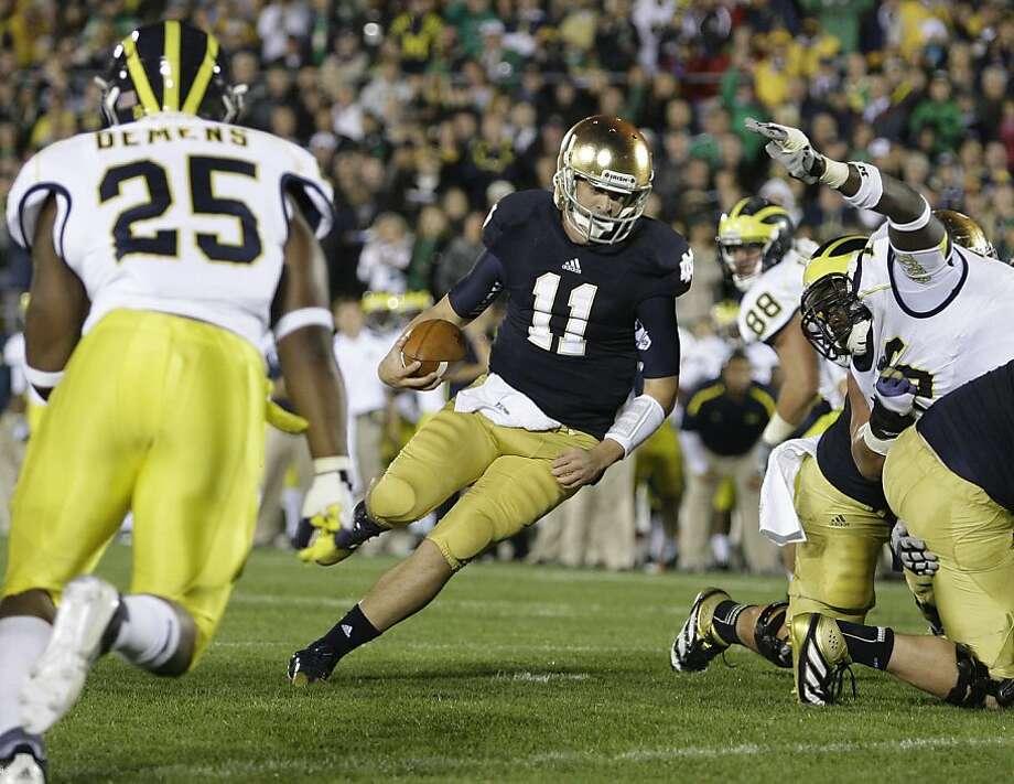 Notre Dame quarterback Tommy Rees runs for a second-quarter touchdown against Michigan. Photo: Julian H. Gonzalez, McClatchy-Tribune News Service