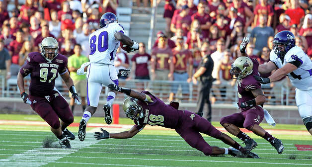 Bobcat defenders try to stop Cordell Roberson as Texas State hosts Stephen F. Austin at Bobcat Stadium on September 22, 2012. Photo: Tom Reel, Express-News / ©2012 San Antono Express-News