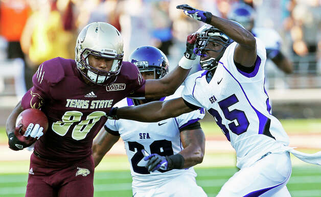 Bobcat receiver Jafus Gaines tries a stiff arm on Calib Hadnot as Texas State hosts Stephen F. Austin at Bobcat Stadium on September 22, 2012. Photo: Tom Reel, Express-News / ©2012 San Antono Express-News