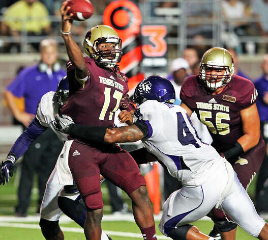 Bobcat quarterback Shaun Rutherford throws the ball under heavy pressure in the fourth quarter as Texas State hosts Stephen F. Austin at Bobcat Stadium on September 22, 2012. Photo: Tom Reel, Express-News / ©2012 San Antono Express-News