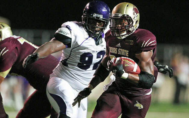 Bobcat running back Marcus Curry slips away from a tackler as Texas State hosts Stephen F. Austin at Bobcat Stadium on September 22, 2012. Photo: Tom Reel, Express-News / ©2012 San Antono Express-News
