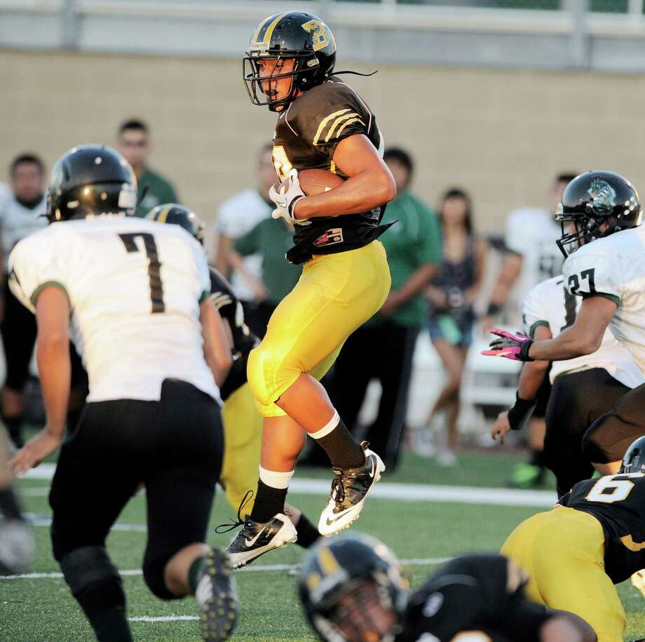 Brennan's Grant Watanabe, center, leaps over Southwest defenders during a high school football game, Saturday, Sept. 22, 2012, at Farris Stadium in San Antonio. Photo: Darren Abate, Express-News