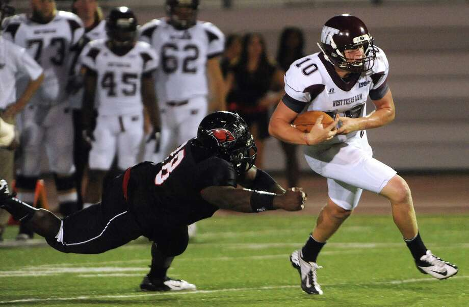 Quarterback Dustin Vaughan of West Texas A&M eludes Incarnate Word defender Michael Tate during college football action at Benson Stadium on Saturday, Sept. 22, 2012. Photo: Billy Calzada, Express-News / © San Antonio Express-News