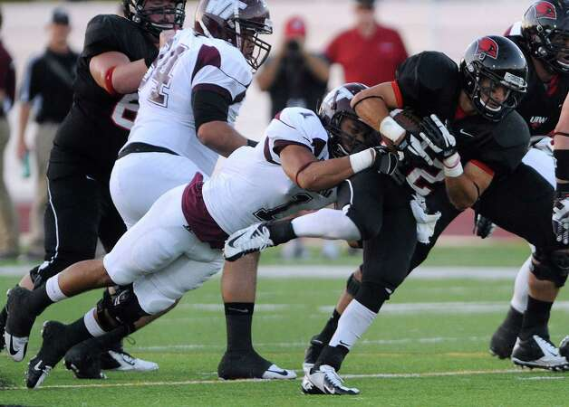 Incarnate Word running back Trent Rios drags West Texas A&M defender Jordan Smith (1) during college football action at Benson Stadium on Saturday, Sept. 22, 2012. Photo: Billy Calzada, Express-News / © San Antonio Express-News