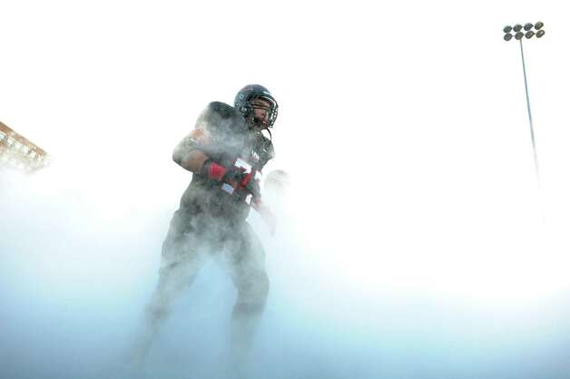 Incarnate Word linebacker Devin Threat emerges from the mist as he runs onto the Benson Stadium field for the game against West Texas A&M on Saturday, Sept. 22, 2012. Photo: Billy Calzada, Express-News / © San Antonio Express-News