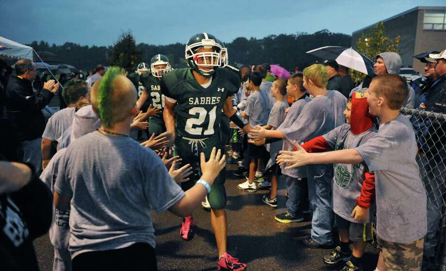Schalmont's #21 Devon Willis leads his team onto the field through the cheers of members of Shalmont's youth football program to meet Broadalbin-Perth Saturday night's game in Rotterdam Sept. 22, 2012.  (John Carl D'Annibale / Times Union) Photo: John Carl D'Annibale / 00019330A