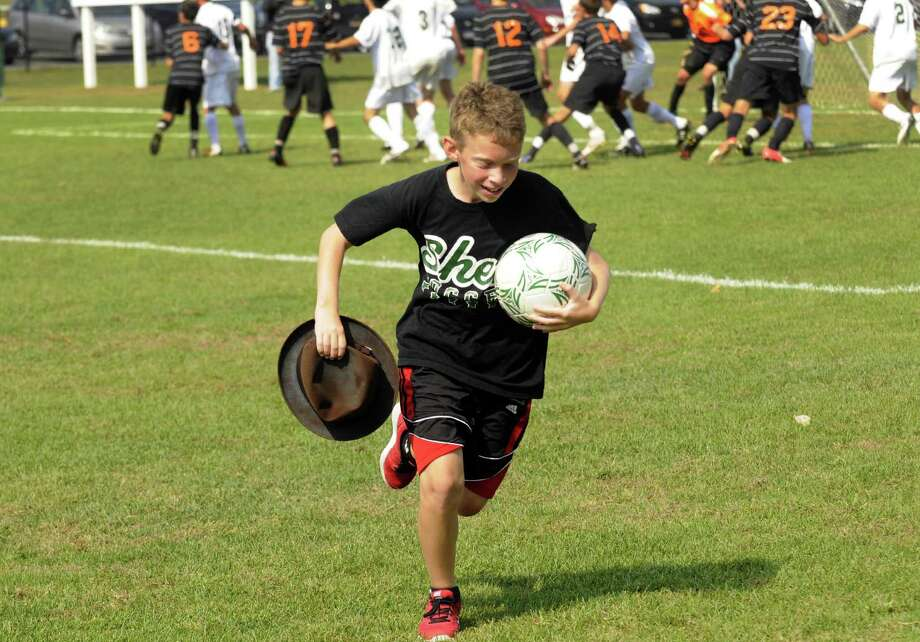 Twelve-year-old ball boy Andy Bindelglass retrieves Times Union photographer Michael P. Farrell's fedora after a gust of wind blew it on to the field during the Shenendehowa-Bethlehem boys' soccer game in Clifton Park, NY Saturday Sept. 22, 2012. (Michael P. Farrell/Times Union) Photo: Michael P. Farrell