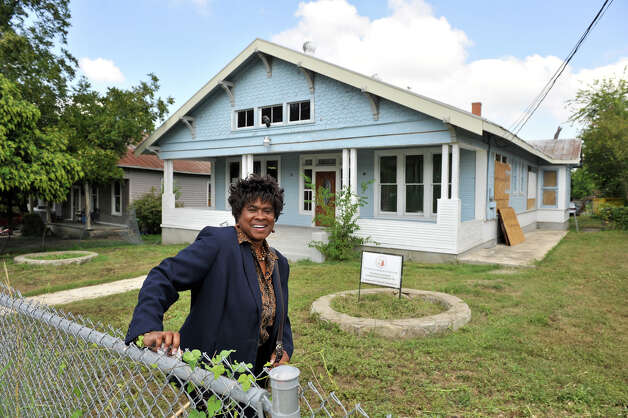 Dee Smith stands in front of the Dignowity Hill bungalow home she bought at auction for $3,200. Grants from the San Antonio Conservation Society are aiding with the restoration costs. Photo: Robin Jerstad, For The Express-News