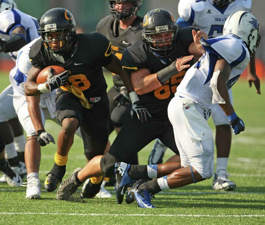 Klein Oak's Jonathan Toth (18) look for running room as teammate Mitchell Montayne provides a block on Dekaney's Deon Booker-Brown during the first half of a high school football game, Saturday, September 22, 2012 at Klein Memorial Stadium in Klein, TX. Photo: Eric Christian Smith, For The Chronicle