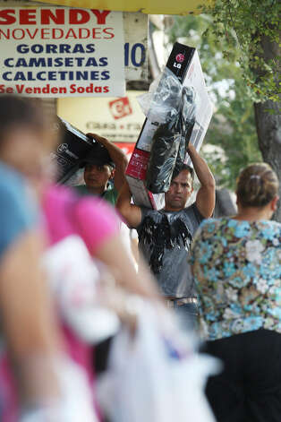 Pedestrians carry LED televisions as they head back to Nuevo Laredo, Mexico after a day of shopping in downtown Laredo, Wednesday, Sept. 19, 2012. Downtown businesses have suffered with sales due to various factors including the drug war across the Rio Grande in Nuevo Laredo and difficulties in crossing the U.S. Customs checkpoints at the international bridge. Photo: Jerry Lara, San Antonio Express-News / © 2012 San Antonio Express-News