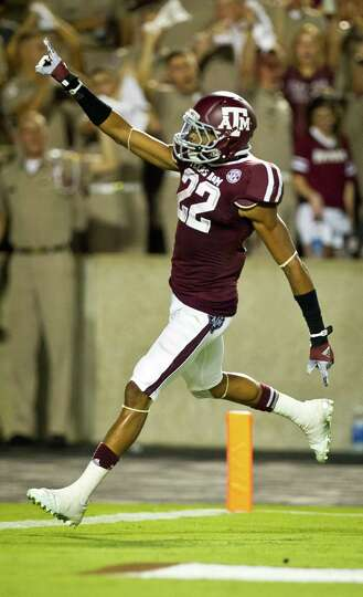 Texas A&M University kick returner Dustin Harris (22) points to the crowd after scoring a touchdown
