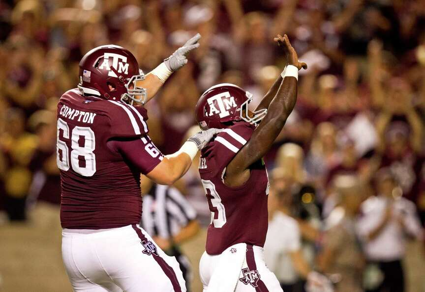 Texas A&M University offensive linesman Ben Compton (68) celebrates with running back Christine Mich
