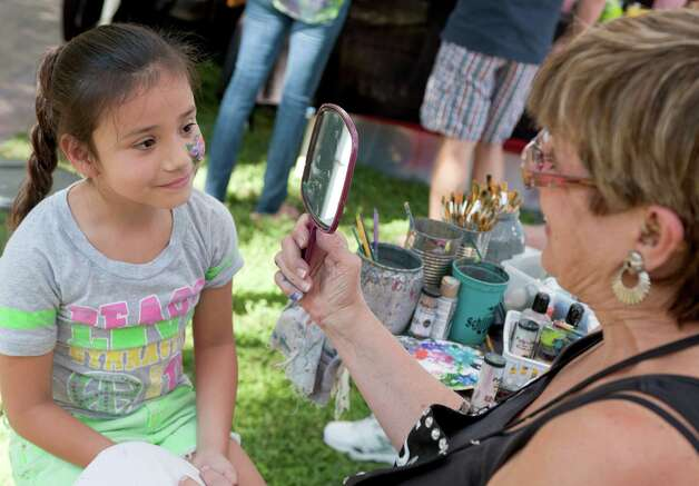Seven-year-old Andrea Garza, left, looks in a mirror after having her face painted by Jean WIlson at Jazz'SAlive, Saturday, Sept. 22, 2012, at Travis Park in San Antonio. Photo: Darren Abate, For The Express-News