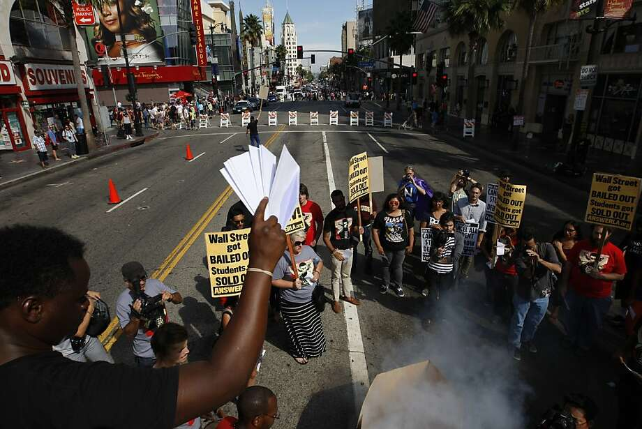 Students symbolically 'burn' their student loan bills and mock bills by throwing them into a box with a smoke machine during a demonstration on Hollywood Boulevard to protest the rising costs of student loans for higher education on September 22, 2012 in the Hollywood section of Los Angeles, California. Citing bank bailouts, the protesters called for student debt cancelations. Photo: David McNew, Getty Images