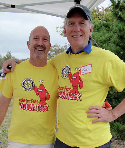 Westport Rotary Club members Steve Lewine and John Hartwell staff the entrance Saturday at the Westport Lobster Fest on Compo Beach. Photo: Mike Lauterborn / Westport News contributed