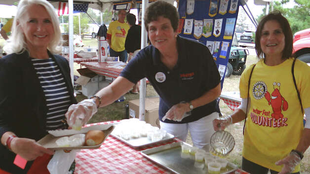 Jenny Clerkin, Jackie O'Brien and Westport Historical Society Executive Director Susan Gold distribute cups of melted butter at the Westport Rotary Club's Lobster Fest. Photo: Mike Lauterborn / Westport News contributed