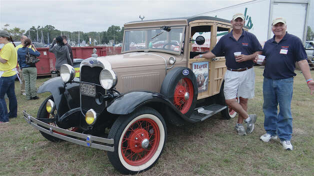 "Bill O'Brien and Baxter Urist, president and co-founder of Beaver Beer, respectively, stand beside O'Brien's 1930 Model A Ford ""Woody"" stationwagon at the Westport Rotary Club's Lobster Fest on Saturday. Photo: Mike Lauterborn / Westport News contributed"