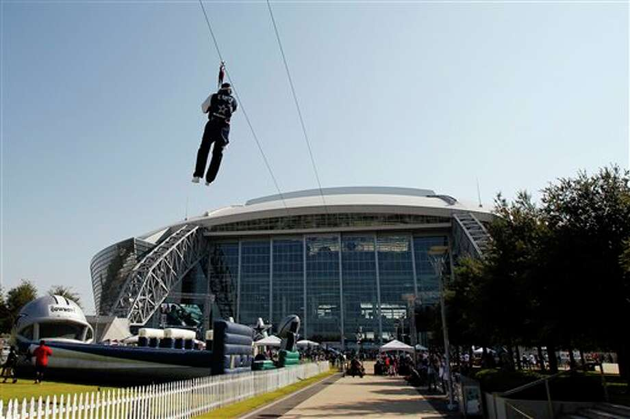 Fans ride a zip line outside Cowboys Stadium before an NFL football game between the Dallas Cowboys and the Tampa Bay Buccaneers, Sunday, Sept. 23, 2012, in Arlington, Texas. (AP Photo/Tim Sharp) Photo: Tim Sharp, Associated Press / FR62992 AP