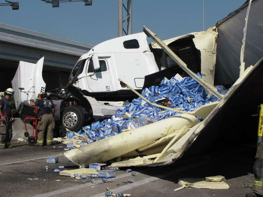 San Antonio firefighters stand in front of a tractor-trailer that jackknifed Sunday morning, spilling a load of beer across the highway and causing an hours-long closure. Photo: Eva Ruth Moravec/Express-News / emoravec@express-news.net