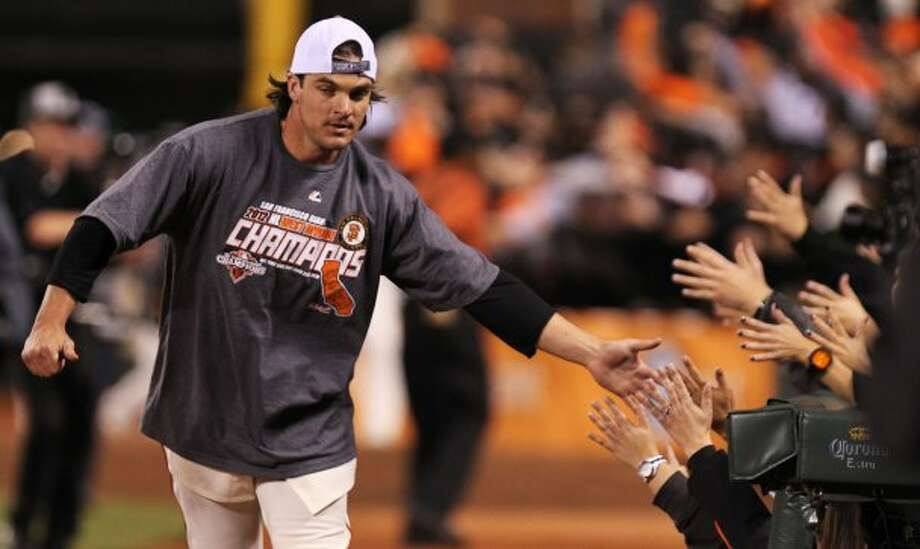 Ryan Theriot shakes hands with the fans as the San Francisco Giants celebrate their 8-4 win over the San Diego Padres that gave them the National League West title Saturday September 22, 2012. In San Francisco California. (Lance Iversen / The Chronicle)