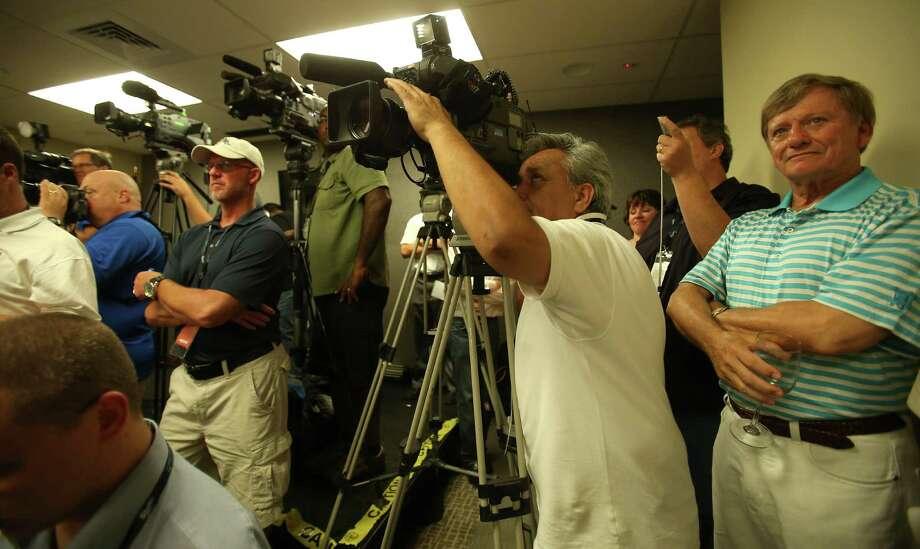 Attorney Rusty Hardin listens as Roger Clemens speaks to the media. Photo: Karen Warren / © 2012  Houston Chronicle
