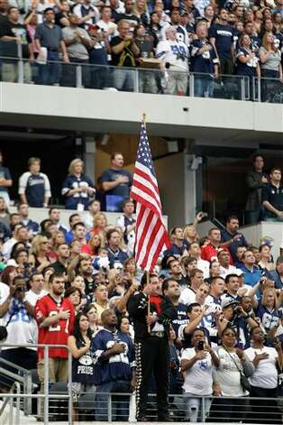 A mariachi member holds an American flag in front of football fans during an NFL football game between the Tampa Bay Buccaneers and Dallas Cowboys Sunday, Sept. 23, 2012, in Arlington, Texas. The NFL is celebrating Hispanic Heritage Month. (AP Photo/LM Otero) Photo: Associated Press