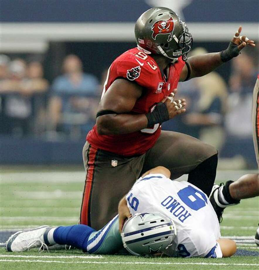 Tampa Bay Buccaneers defensive tackle Gerald McCoy, top, celebrates after teammate Michael Bennett sacked Dallas Cowboys quarterback Tony Romo (9) during the first half of an NFL football game on Sunday, Sept. 23, 2012, in Arlington, Texas. (AP Photo/LM Otero) Photo: Associated Press