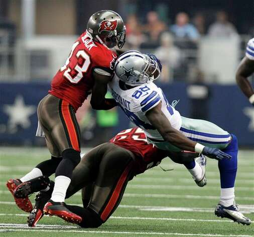 Dallas Cowboys wide receiver Dez Bryant (88) is tackled by Tampa Bay Buccaneers free safety Ahmad Black (43) and Aqib Talib (25) during the first half of an NFL football game on Sunday, Sept. 23, 2012, in Arlington, Texas. (AP Photo/LM Otero) Photo: Associated Press