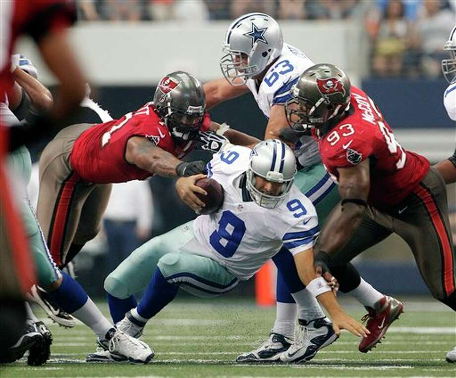 Dallas Cowboys' Tony Romo (9) is sacked by Tampa Bay Buccaneers defensive end Michael Bennett (71) and Gerald McCoy (93) during the second half of an NFL football game on Sunday, Sept. 23, 2012, in Arlington, Texas. (AP Photo/Tim Sharp) Photo: Associated Press