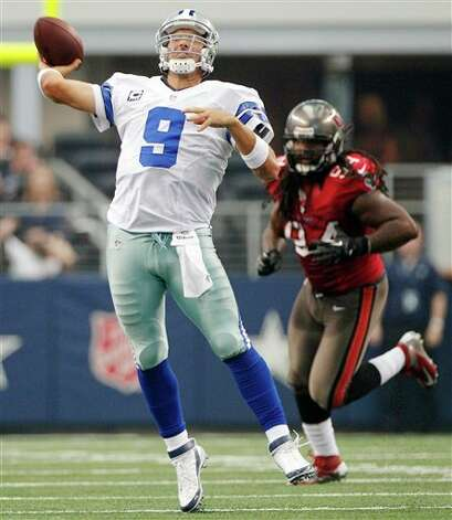 Dallas Cowboys quarterback Tony Romo (9) makes a long pass as Tampa Bay Buccaneers defensive end Adrian Clayborn (94) moves in during the second half of an NFL football game on Sunday, Sept. 23, 2012, in Arlington, Texas. (AP Photo/Tim Sharp) Photo: Associated Press