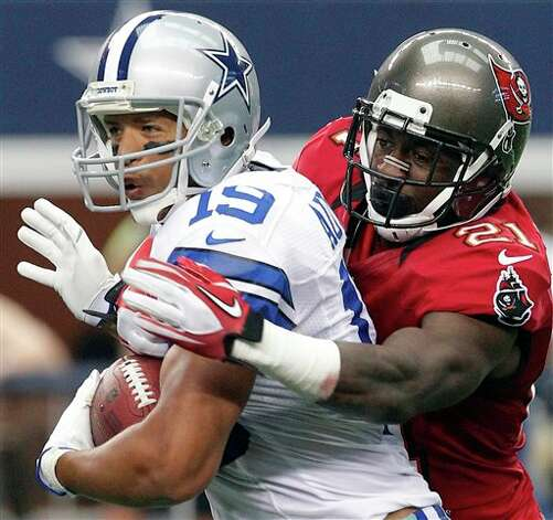 Dallas Cowboys wide receiver Miles Austin (19) is tackled by Tampa Bay Buccaneers defensive back Eric Wright (21) during the second half of an NFL football game on Sunday, Sept. 23, 2012, in Arlington, Texas. (AP Photo/Tim Sharp) Photo: Associated Press