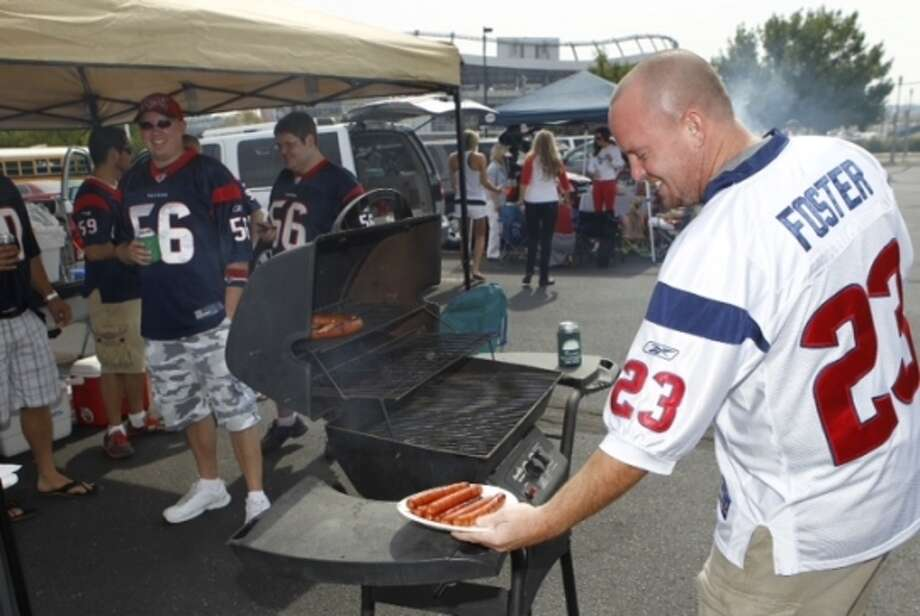 Houston Texans fan Tony Fries, of Friendswood, cooks on a grill as he and his friends tailgate outside Sports Authority Field. ( Brett Coomer / Houston Chronicle ) (Brett Coomer / Houston Chronicle)