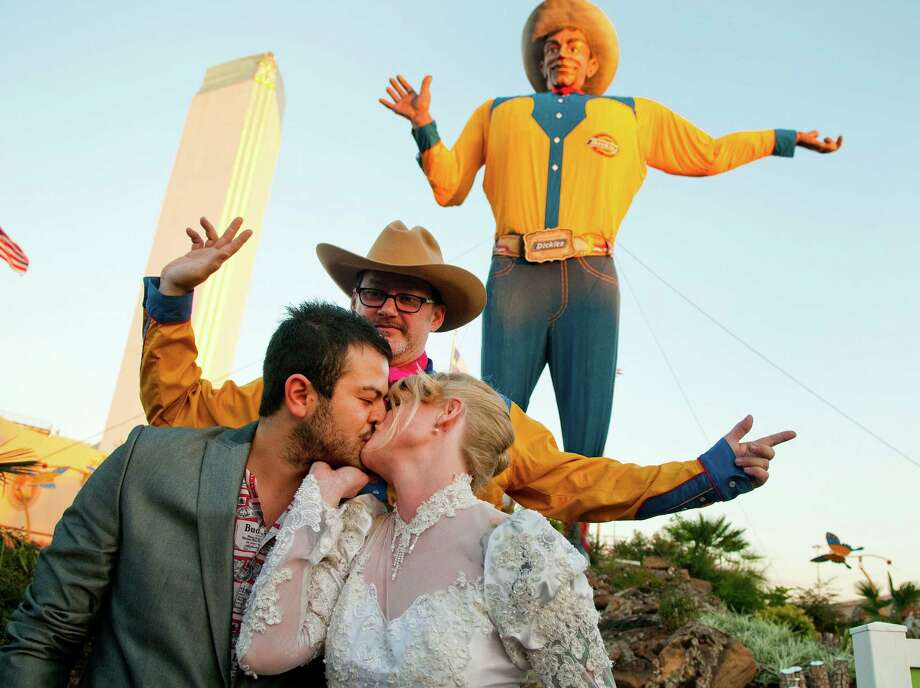"During a portrait, Jose Luis Martinez Hernandez of Mexico City kisses his wife, Sara Rice of Dallas after their friend Tom ""Pinky Diablo"" Sale of Ennis conducted their wedding ceremony in front of Big Tex at the State Fair of Texas on Oct. 12, 2010.  Photo: BRENDAN SULLIVAN/Staff Photograp / 10005717B"