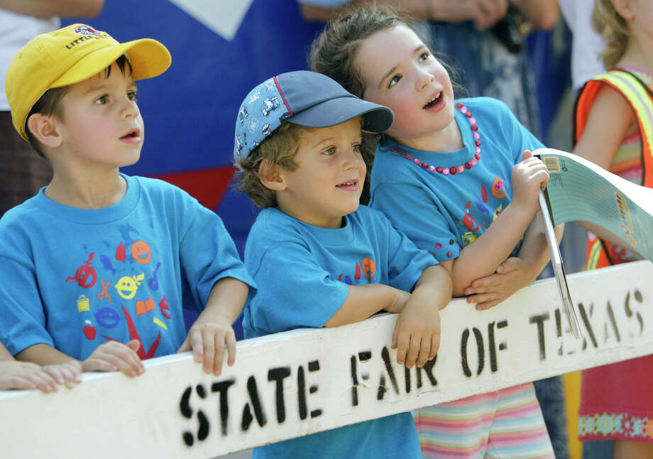Youngsters, from left, Brady Hernandez, 4,  William Holtby, 4, and Lilly Gilbreath, 4, watch as workers hoist Big Tex, a 52-foot-tall talking cowboy figure into place for the State Fair of Texas, Tuesday, Sept. 27, 2005. Photo: MATT SLOCUM, AP / AP
