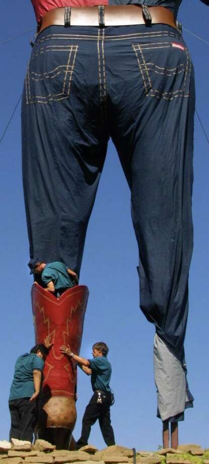 Debra Duron, left, and Douglas Mortenson, right, holds Big Tex's boot as Tim Thibodeaux, top, tucks in the pant leg Monday, Sept. 23, 2002. Photo: IRWIN THOMPSON, AP / DALLAS MORNING NEWS