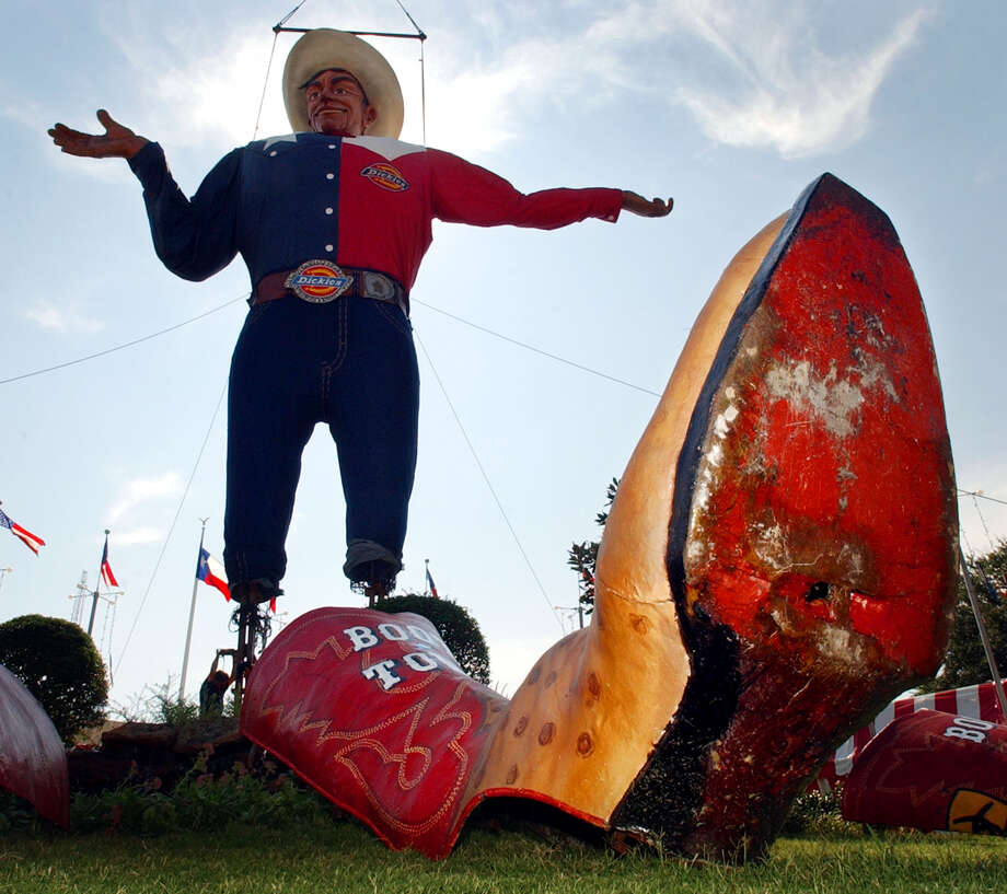 "State Fair of Texas icon ""Big Tex,""  hangs from a crane as workers at the base of the structure mount it to the ground, Monday, Sept. 22, 2003, in Dallas. ""Big Tex"" is a 52-foot structure that speaks, greeting fair-goers to the fair ground for the Texas State Fair that begins Sept 26 and runs through Oct. 19. (AP Photo/Tony Gutierrez)   HOUCHRON CAPTION (09/23/2003):  The State Fair of Texas' official mascot, Big Tex, hangs from a crane as workers secure the base of the structure to the ground Monday in Dallas. The 52-foot character greets fairgoers every year with a booming ""Howdy, folks!"" The State Fair begins Friday and runs through Oct. 19. Photo: TONY GUTIERREZ, AP / AP"