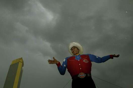 Big Tex stands tall as rain clouds pass overhead Wednesday, Oct. 3, 2007, at the State Fair of Texas in Dallas, Texas. Early-morning rain kept the number of visitors down and workers were trying to stay dry as they prepared for the day.   (AP Photo/The Dallas Morning News, Guy Reynolds) ** NO SALES, MAGS OUT, TV OUT, INTERNET USE BY AP MEMBERS ONLY ** Photo: Guy Reynolds, AP / THE DALLAS MORNING NEWS