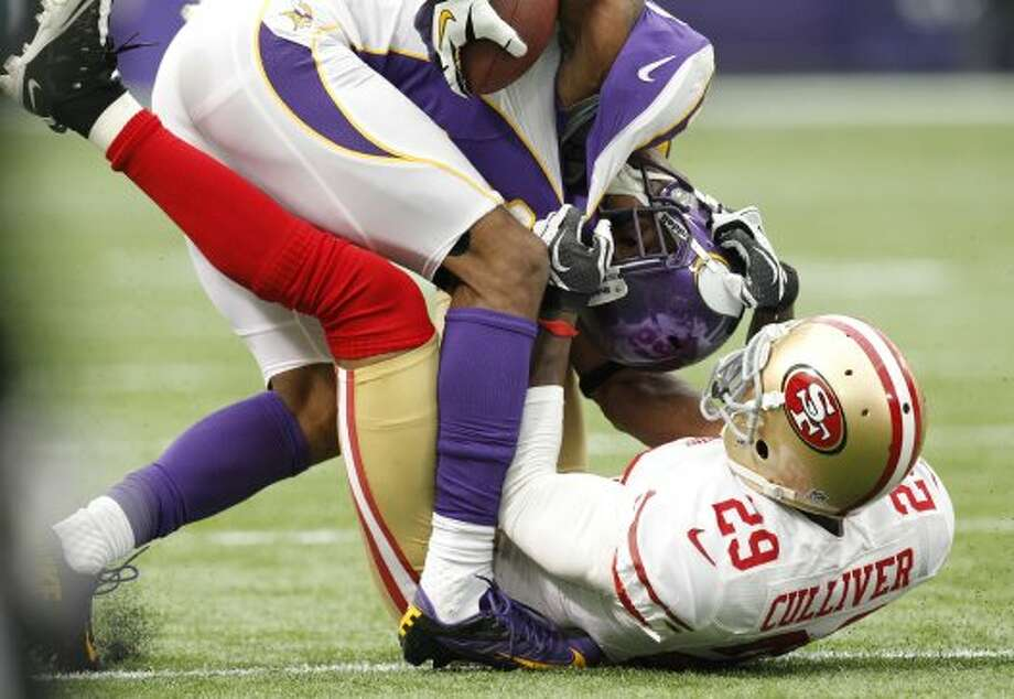 Minnesota Vikings wide receiver Percy Harvin, left, is tackled by San Francisco 49ers defensive back Chris Culliver after making a reception during the first half of an NFL football game Sunday, Sept. 23, 2012, in Minneapolis. (Genevieve Ross / Associated Press)