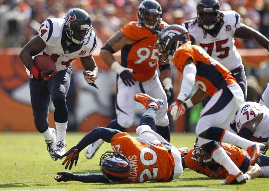 Texans running back Ben Tate leaps over Broncos strong safety Mike Adams during the first quarter. (Brett Coomer / © 2012  Houston Chronicle)