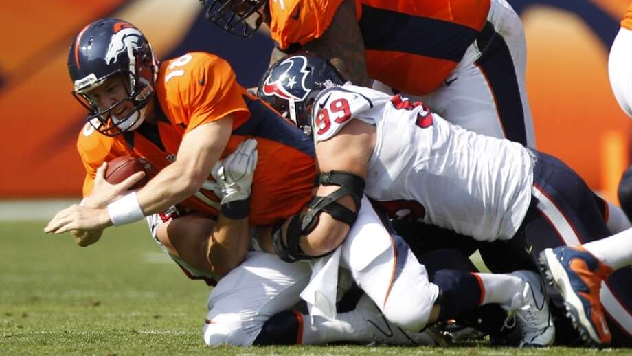 Texans defensive end J.J. Watt gets a hold of Broncos quarterback Peyton Manning during the first quarter. (Brett Coomer / © 2012  Houston Chronicle)