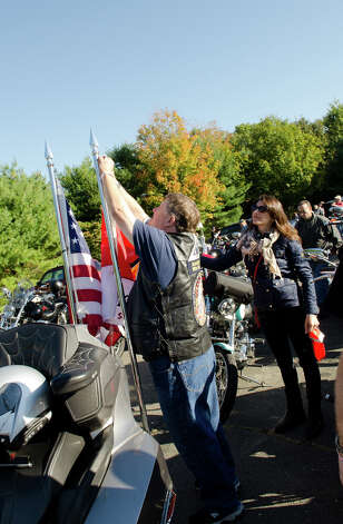 Ed Parshall, a Patriot Guard Rider of Waterbury, fastens the Honor and Remember Flag on his bike during the fourth annual Thunder on the Sound Motorcycle Ride and BBQ benefiting the Brian Bill Memorial Fund on Sunday, Sept. 23, 2012 in Stamford. Assisting Parshall is Amy Bill Kutney, Brian Bill's sister. Bikers assembled in the park and ride lot at Exit 35 off the Merritt Parkway. Photo: Amy Mortensen / Connecticut Post Freelance